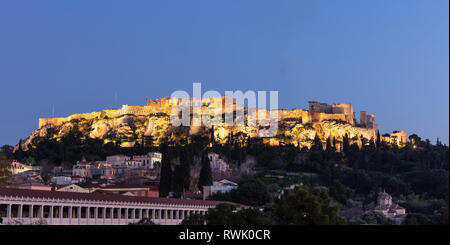 Acropolis of Athens Greece rock and Parthenon illuminated, blue sky background late in the evening. View from Monastiraki area - Stock Photo