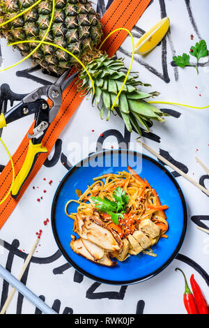 Stir fry noodles traditional Chinese wok, chopsticks, ingredients. Asian noodles with vegetables and chicken. Wok noodles. Copy space. Top view. - Stock Photo