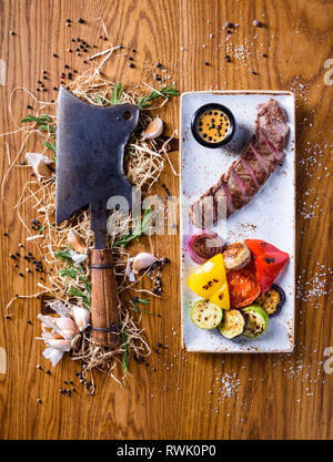 Barbecue rib eye Steak with a choper. Dry aged entrecote Steak with grilled vegetables. Top view, copy space. - Stock Photo