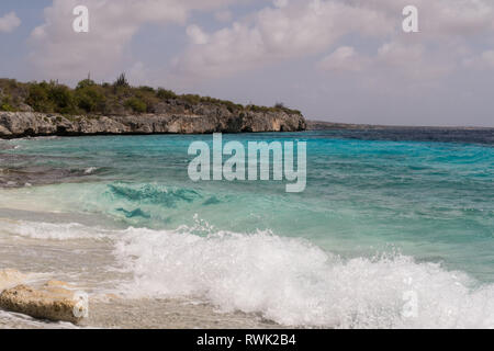 Waves breaking on a beutiful beach of broken corals on the west coast of the tropical island Bonaire in the Caribbean