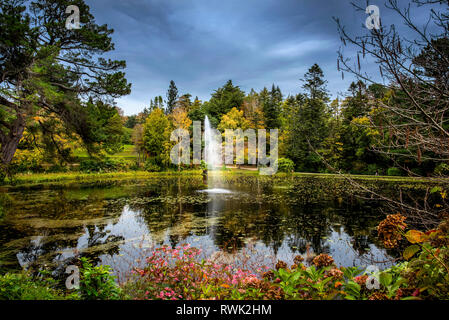 A fountain in a pond surround by blossoming plants and trees, Powerscourt Estate; Enniskerry, County Wicklow, Ireland - Stock Photo