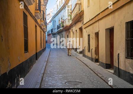 An elderly man walks down the narrow street between residential buildings; Cadiz, Andalusia, Spain - Stock Photo