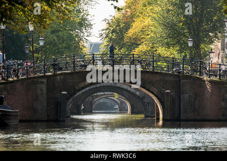 Several stone bridge arch ways along a canal with several bikes on railing; Amsterdam, Netherlands - Stock Photo