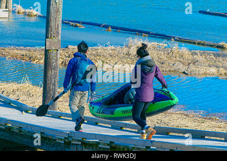 Young Asian couple carrying an inflatable kayak along a wooden ramp. Grant Narrows Regional Park, Pitt Meadows, British Columbia, Canada - Stock Photo