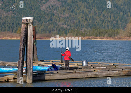 Middle aged woman in bright winter coat standing on a pier with kayak paddles. Grant Narrows Regional Park, Pitt Meadows, B.C., Canada - Stock Photo