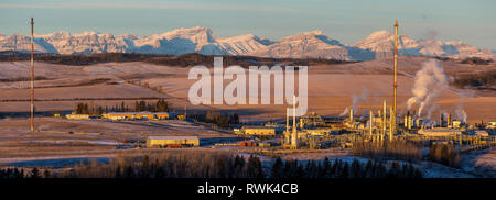 Panorama of gas plant at sunrise with warm sunlight on snow-covered mountain range and foothills in the background with blue sky, West of Cochrane - Stock Photo