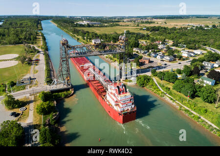 Aerial view of large laker ship navigating under a metal lift bridge in a canal with blue sky; Thorold, Ontario, Canada - Stock Photo