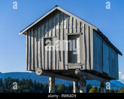 Wooden house on stilts with the Coast mountains in the background; Vancouver, British Columbia, Canada - Stock Photo