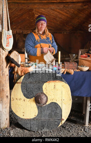 Reenactor in period costume surrounded by a variety of hand-crafted items that would have typically been traded when L'Anse aux Meadows was settled by the Vikings around the year 1000. Norstead Viking Village and Port of Trade, L'Anse aux Meadows, Newfoundland, Canada - Stock Photo