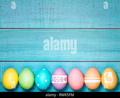 Colorful Easter Eggs arranged in a row on a blue background. - Stock Photo