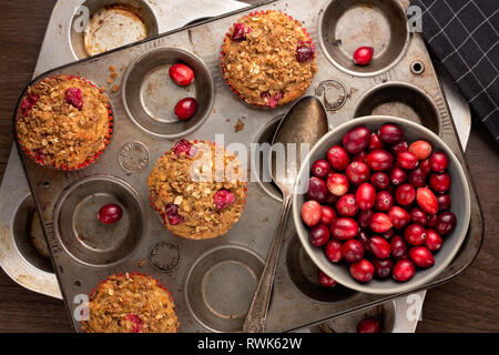 Freshly baked cranberry muffins with oatmeal crumble topping in a rustic muffin tin. - Stock Photo