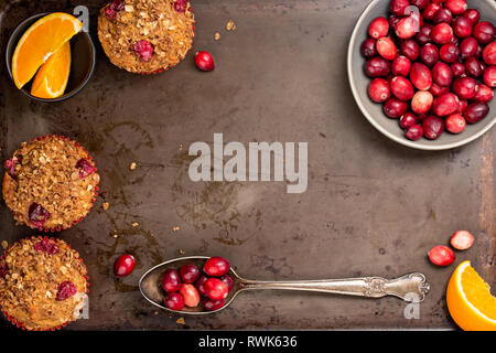 Freshly baked cranberry muffins on a rustic baking pan with cranberries and orange slices. - Stock Photo