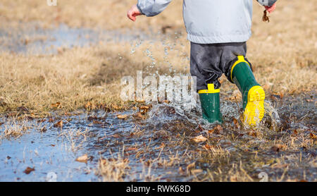 Toddler running in puddles wearing rainboots.