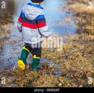 Little boy walking through puddles in the grass wearing rainboots. - Stock Photo