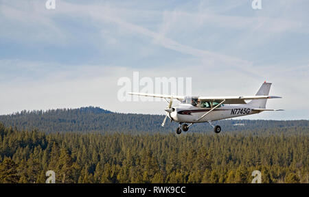 A small Cessna aircraft practices touch and go landings on an airstrip in the Cascade Mountains, Oregon - Stock Photo