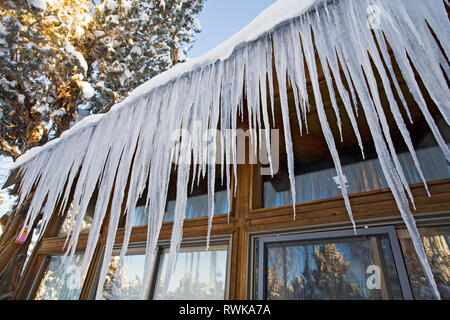 Giant icicles hang from an overhanging roof eave on a wooden house in Bend, Oregon, after a major winter snowfall. - Stock Photo