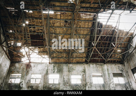 Old abandoned, ruined industry, factory, warehouse; broken and destroyed roof, windows; sunlight and shadow, Hualien, Taiwan - Stock Photo