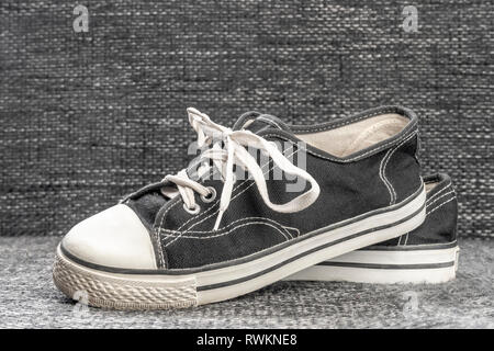 Black white rubber cloth old familiar sneakers on a textile background - Stock Photo