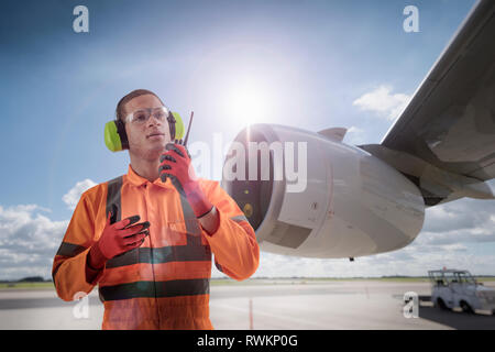 Composite image of airport worker speaking on walkie talkie in front of A380 engine - Stock Photo