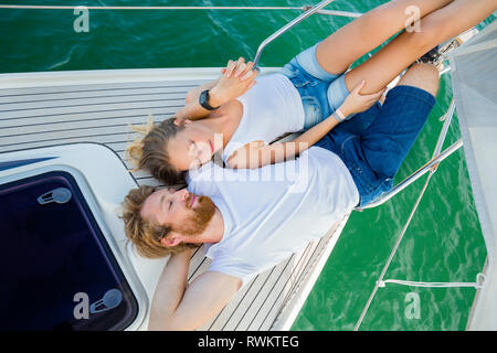 Young couple lying on sailboat on Chiemsee lake, overhead view, Bavaria, Germany - Stock Photo