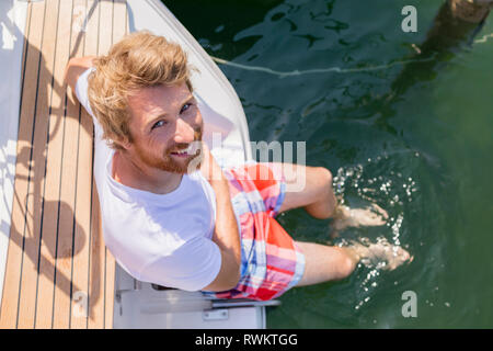 Young man sitting on sailboat on Chiemsee lakeside, overhead portrait, Bavaria, Germany - Stock Photo