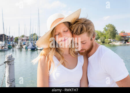 Romantic young couple on sailboat on Chiemsee lakeside, Bavaria, Germany - Stock Photo