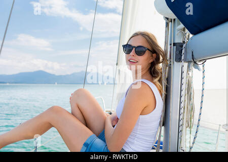 Young woman wearing sunglasses on sailboat on Chiemsee lake, portrait, Bavaria, Germany - Stock Photo