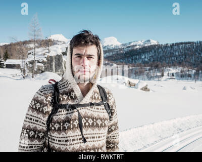 Mid adult man in hooded sweater in snow covered mountain landscape, portrait, Alpe Ciamporino, Piemonte, Italy - Stock Photo