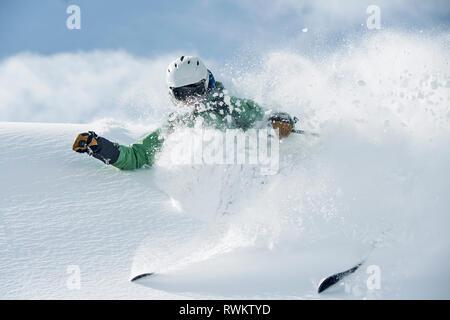 Male skier speeding down snow covered mountain, Alpe-d'Huez, Rhone-Alpes, France - Stock Photo