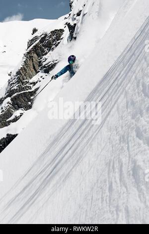 Male skier speeding down steep mountainside, Alpe-d'Huez, Rhone-Alpes, France - Stock Photo