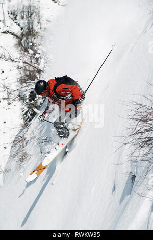 Male skier speeding down vertical mountainside, Alpe-d'Huez, Rhone-Alpes, France - Stock Photo