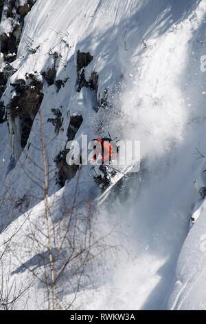 Male skier speeding down rugged vertical mountainside, Alpe-d'Huez, Rhone-Alpes, France - Stock Photo
