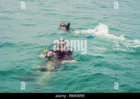 Divers on the surface of water ready to dive - Stock Photo