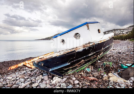 Abandoned old fishing boat on the coastline on a moody winter day in Gumusluk, Bodrum, Turkey. - Stock Photo