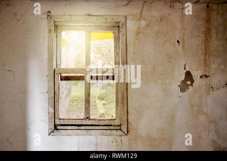 Interior of a ruined house with old, dirty and cracked white wall and a broken vintage window frame viewing a green meadow field landscape - Stock Photo