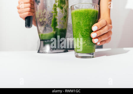 Woman's hands with white manicure holding blender and glass of freshly made green smoothie on kitchen table, close-up. - Stock Photo