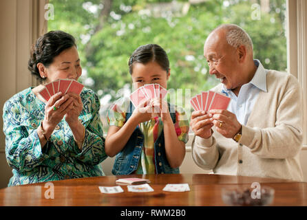 Young girl having fun playing a card game with her grandparents. - Stock Photo