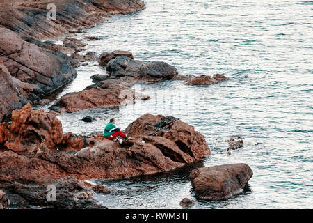 Angler fisherman sitting on the rocks and fishing with rods near the seaside. - Stock Photo