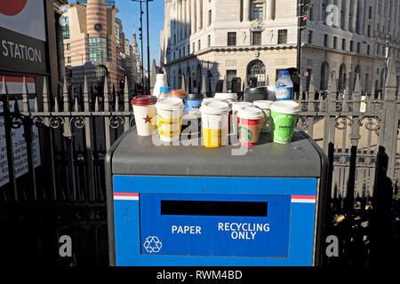 Paper and plastic empty cups and plastic bottles standing on a Paper Recycling Only waste bin Bank tube station in the City of London UK  KATHY DEWITT - Stock Photo