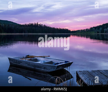 A wooden rowboat sits beside a dock on a tranquil lake reflecting the pink of a sunset, Lac Le Jeune Provincial Park - Stock Photo