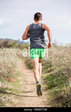 Runner jogging on cliff top, Santa Barbara, California, USA - Stock Photo