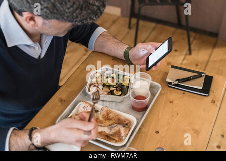 Businessman using smartphone and eating grilled chicken in restaurant - Stock Photo
