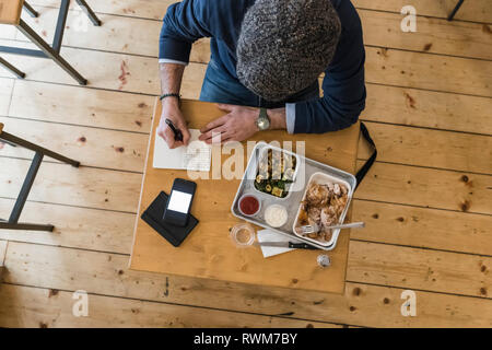 Businessman writing notes over lunch of grilled chicken and vegetables in restaurant - Stock Photo