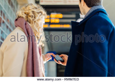 Couple checking smartphone at train station, Firenze, Toscana, Italy - Stock Photo