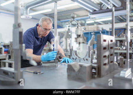Engineer measuring part in engineering factory - Stock Photo