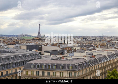 Paris rooftops view and Eiffel Tower in a cloudy day, horizon in France - Stock Photo