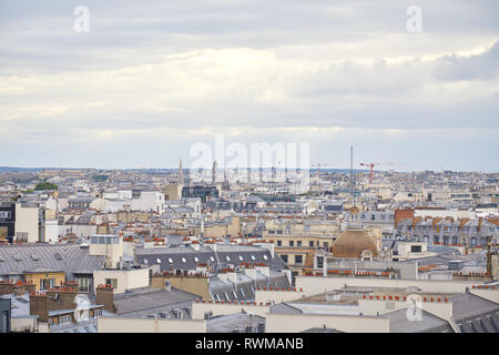 Paris rooftops view and skyline in a cloudy day in France - Stock Photo