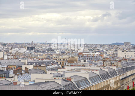 Paris rooftops view and city skyline in a cloudy day with sun beam in France - Stock Photo