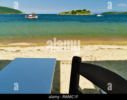 View to sandy beach with boats in crystal clear water from a restaurant in Kavala Greece. - Stock Photo