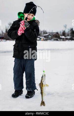 A young boy catching a Walleye while ice fishing on Lake Wabamum during a winter family outing; Wabamun, Alberta, Canada - Stock Photo